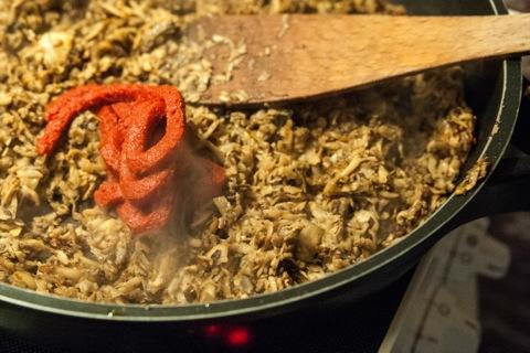 Bild: Die geschnitzelten Chamignongs in heißem Rapsöl anbraten, würzen und mit Tomatenmark binden.