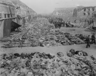 Bild: Leichen von Häftlingen auf dem Gelände der Boelcke-Kaserne in Nordhausen. Aufnahme vom 13.04.1945. Dieses Bild wurde von einem Mitglied der United States Army während dessen Ausführung seiner Dienstpflichten erstellt. Als eine Arbeit der US-Regierung ist dieses Bild public domain.