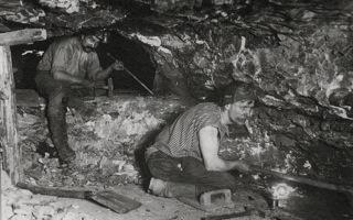 Bild: Bergleute im Mansfelder Revier im Jahre 1911 vor Streb beim Bohren der Schießlöcher. Hier war es der Hermannschacht bei Helfta, aber die Arbeitsbedingungen waren auf allen Schächten der MANSFELD vergleichbar. Eine persönliche Schutzausrüstung gab es für die Bergleute damals nicht. Dieses Bild ist gemeinfrei, weil seine urheberrechtliche Schutzfrist abgelaufen ist.