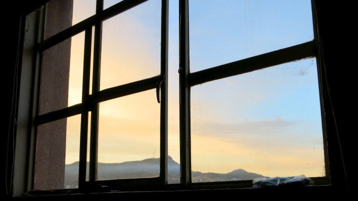 Morning sunlight on the surrounding mountains as seen from my bed.