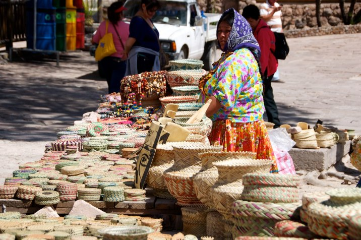 A Tarahumara woman and a table full of baskets and other weavings.