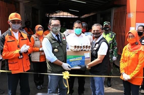 Gubernur Jabar, Ridwan Kamil bersama Wali Kota Cimahi Ajay M Priatna   saat menyerahkan bantuan pangan di Kantor Pos Cimahi, Jalan Gatot Subroto, Kota Cimahi, Minggu (19/4/2020).