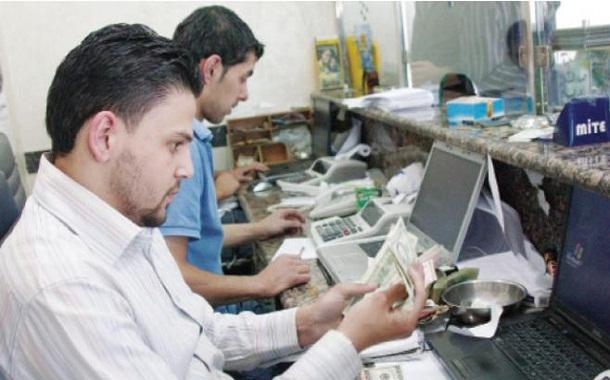 صيرفيان يحصيان أموالا في أحد المحال في عمان - (الغد)
