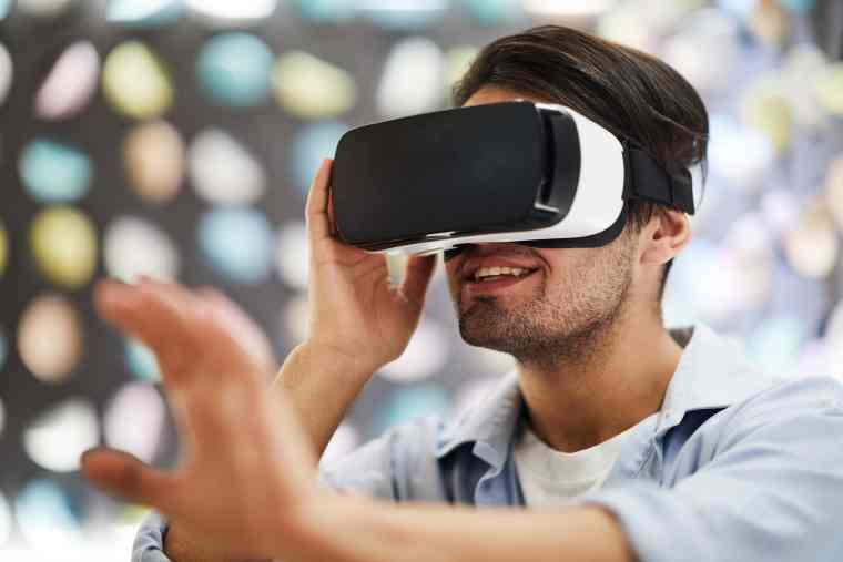 Young happy man in vr goggle enjoying virtual travel and touching new three dimension reality