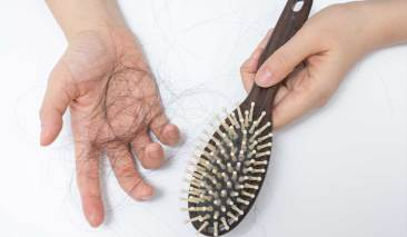 woman showing hair loss in hair bruch