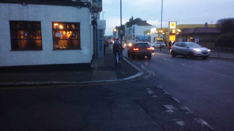 A cyclist with no lights using the pavement, Queens Road, Hastings.