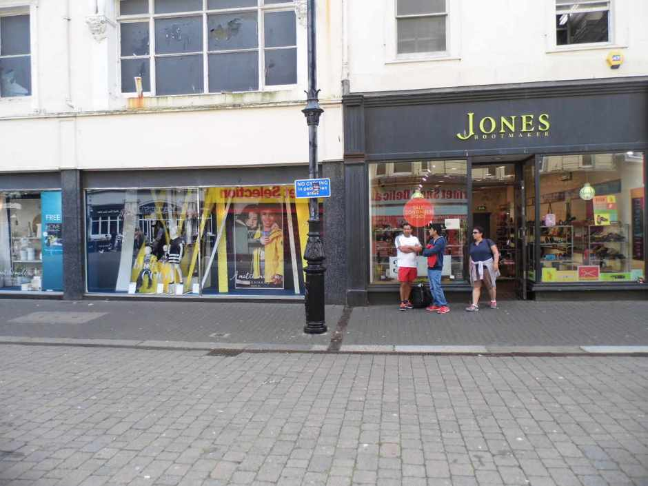 A sign facing the swet shop outside Jones shoe shop.