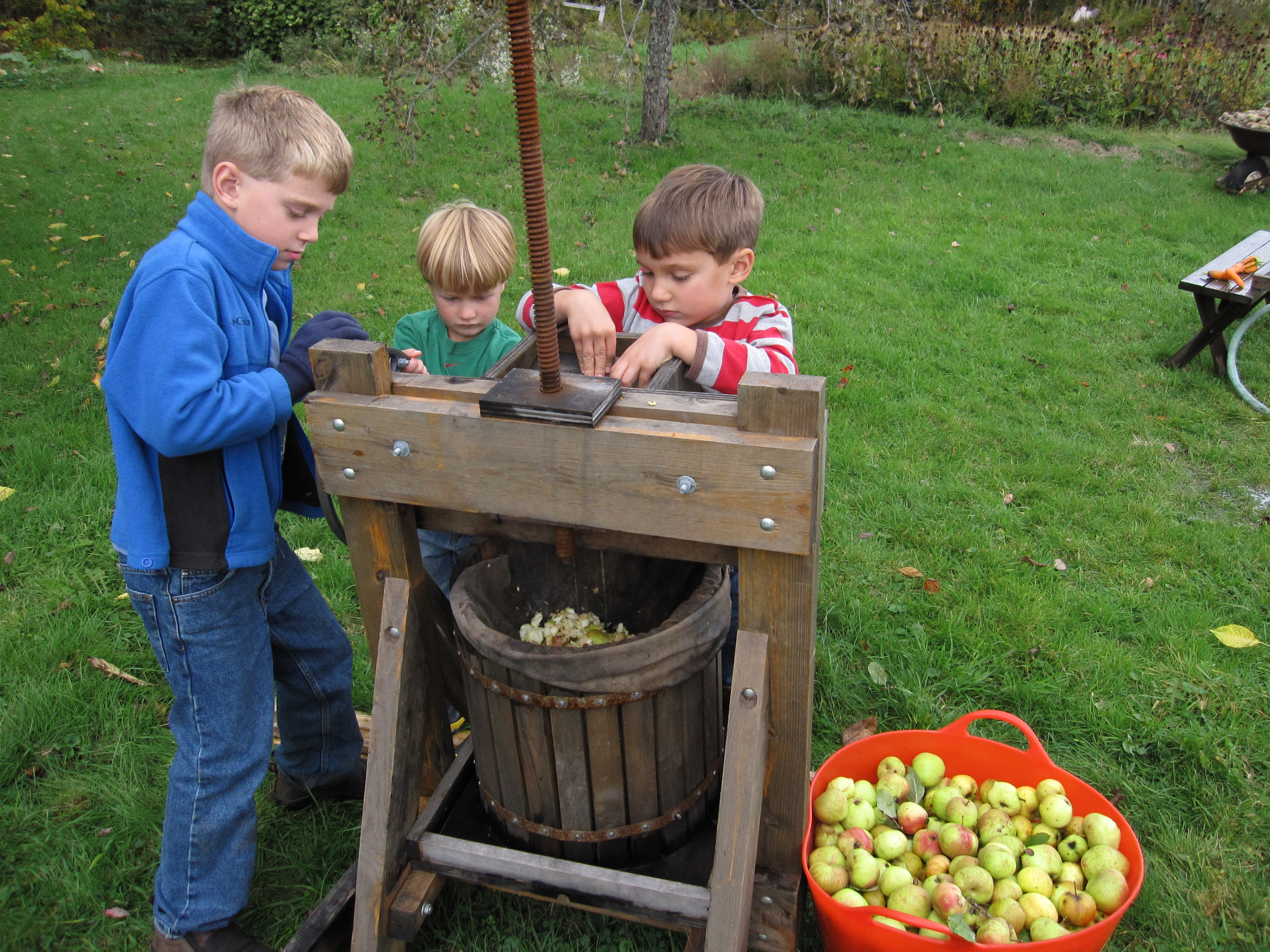 Eli and his cousins, getting the cider press warmed up for next Saturday's cider pressing at the farm.