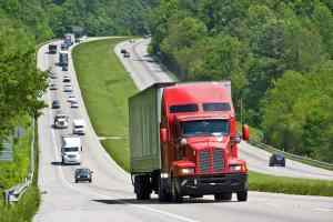 Red Semi Truck Climbing Hill On Interstate Highway