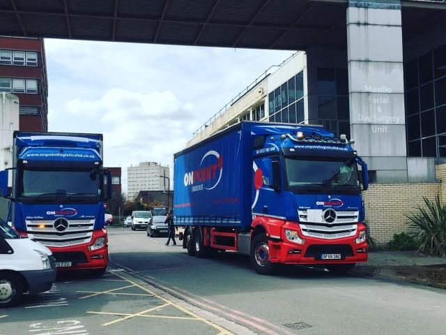 Onpoint Logistics iconic red and blue vehicles delivering to a hospital
