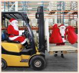 Santa dressed in red driving a forklift truck whilst another santa loads up Christmas presents to the front