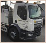 White KJ Bromell truck parked at their depot on a bright day