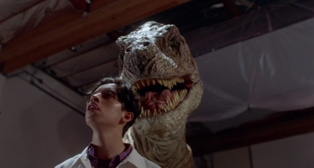 A still image from Tammy and the T-Rex, which shows a Tyrannosaurus Rex hovering ominously behind a pizza delivery man.
