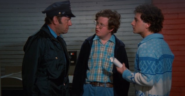 A still shot taken from the 1982 horror film Pieces. It shows two young men speaking with a police officer.   Reviews in Retrospect: Pieces (1982).