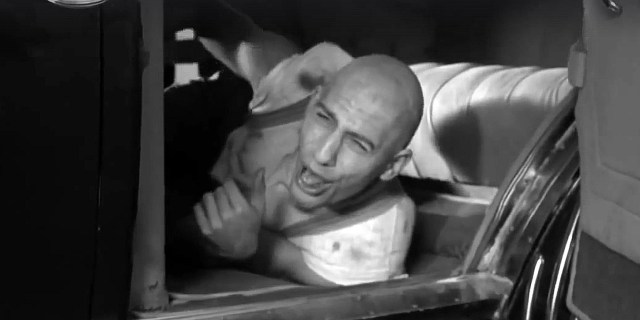 A screen shot taken from the 1968 horror film 'Spider Baby'. It shows a young Sid Haig, as the character 'Ralph', laying on the floor of a car.  The Way Back Machine: Spider Baby (1968)