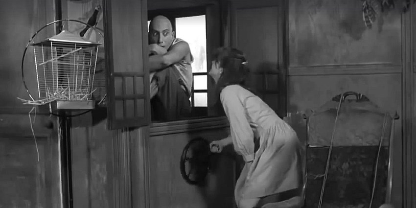 A screencap from the 1968 film 'Spider Baby'. It shows a young woman controlling a dumbwaiter, while Sid Haig rides inside of it. The Way Back Machine: Spider Baby (1968).