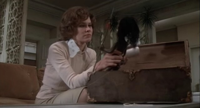 Karen Black as she appears in the 1975 horror film 'Trilogy of Terror'. In the image, she is examining a small, tribal-looking doll.