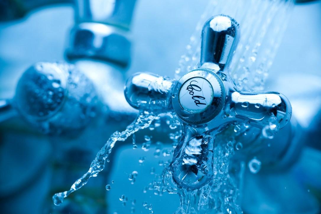 Ein Wasserhahn unter fließendem Wasser mit der Aufschrift Cold.