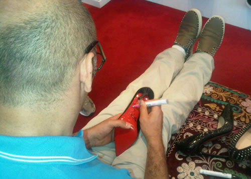 Christian Louboutin signing Rihanna's shoes