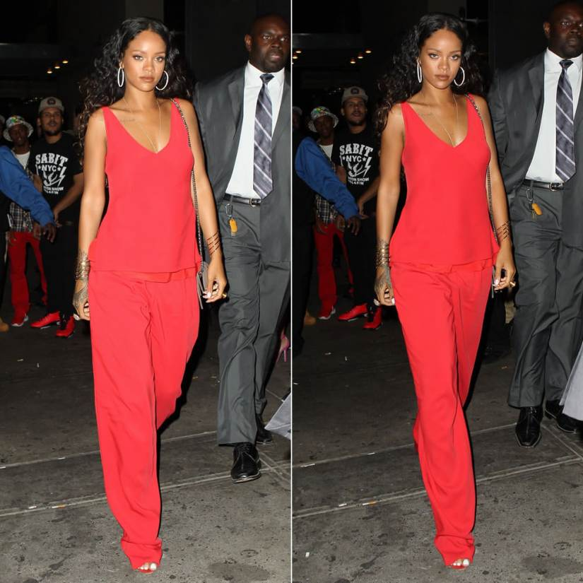 Rihanna wearing Edun red bias cut tank top and pleated trousers, Manolo Blahnik Chaos red ankle-strap sandals, Versace Medusa cocktail rings, Gucci Soho taupe handbag