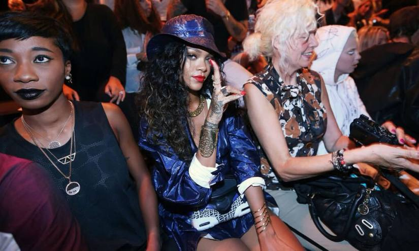 Rihanna at Alexander Wang Spring/Summer 2015 show wearing T by Alexander Wang blue bucket and jacket, Alexander Wang Spring 2015 orange cutout wedge sandals and foldover clutch, Ana Khouri pearl ring and Lola cuff bracelet, Lynn Ban chevron ring and Arabesque wrought iron cuff, Jacquie Aiche lapis outward trinity bodychain