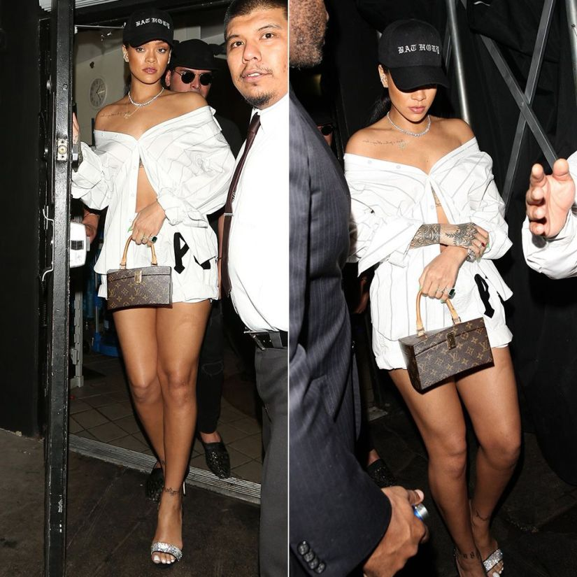 Rihanna Vetements striped button shirt, Fenty x Puma logo white shorts, Giuseppe Zanotti Sophie suede crystal slingback sandals, Hearts on Fire three prong diamond necklace and diamond stud earrings, Louis Vuitton x Frank Gehry twisted box handbag, Bathory cap