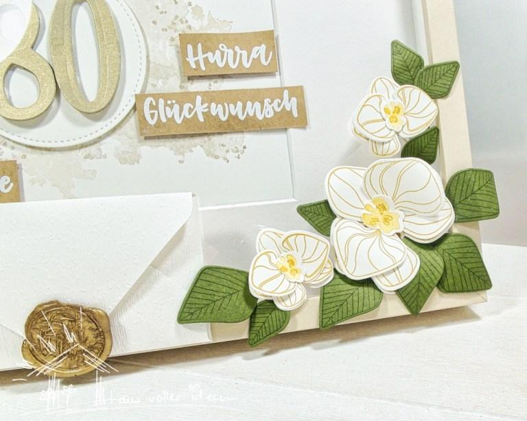 gesiegelter Umschlag mit Gutschein am Bilderrahmen mit Orchideen verziert