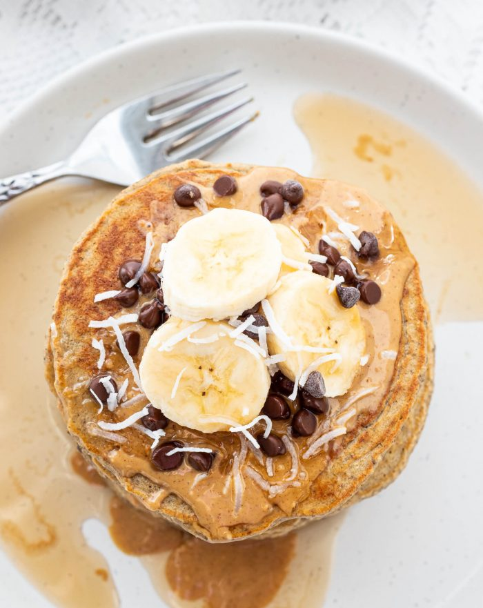 stack of protein pancakes with banana, peanut butter and chocolate chips