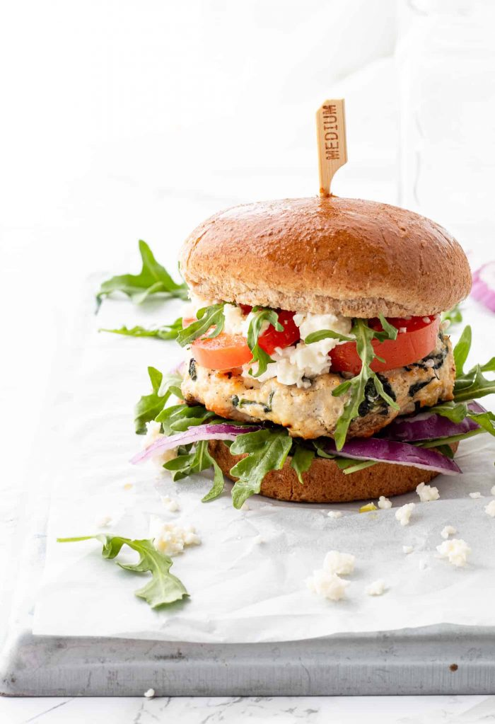 A chicken burger with fresh greens and tomatoes