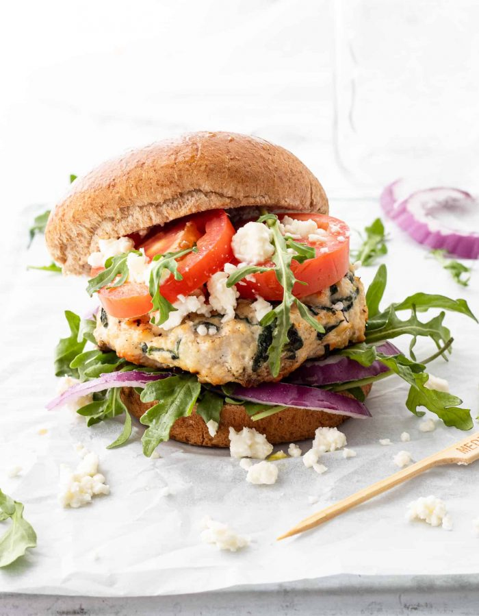 A chicken feta burger served with fresh toppings