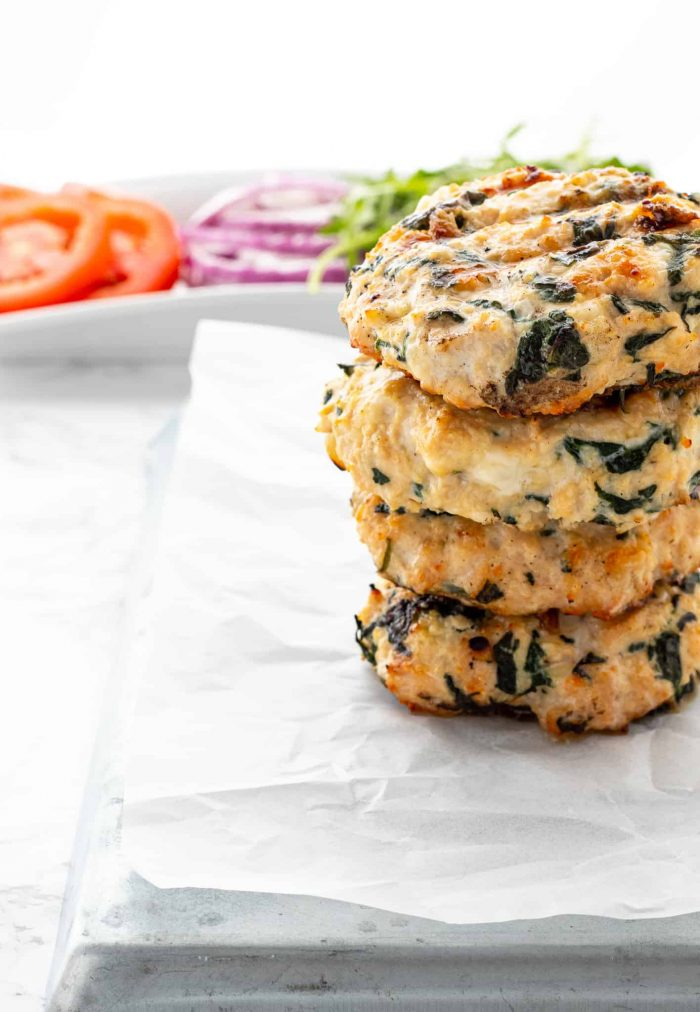 Four chicken feta burger patties stacked on top of each other