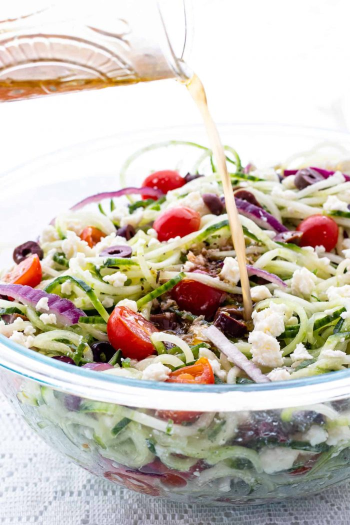 pouring Greek salad dressing on cucumber salad