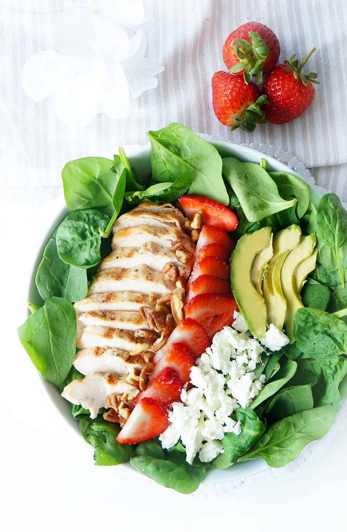 Ingredients for strawberry spinach salad in a bowl