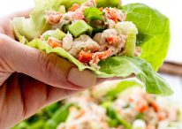 holding tuna lettuce wrap with plate of lettuce wraps in background