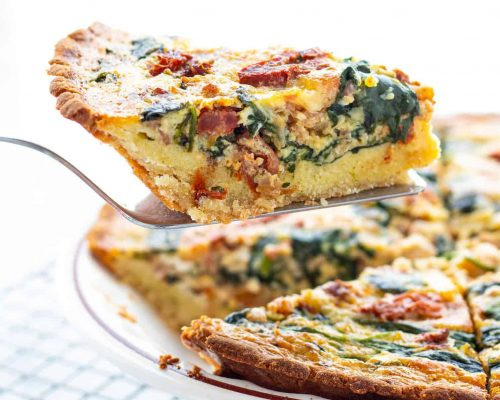 slice of low carb spinach bacon quiche on spatula