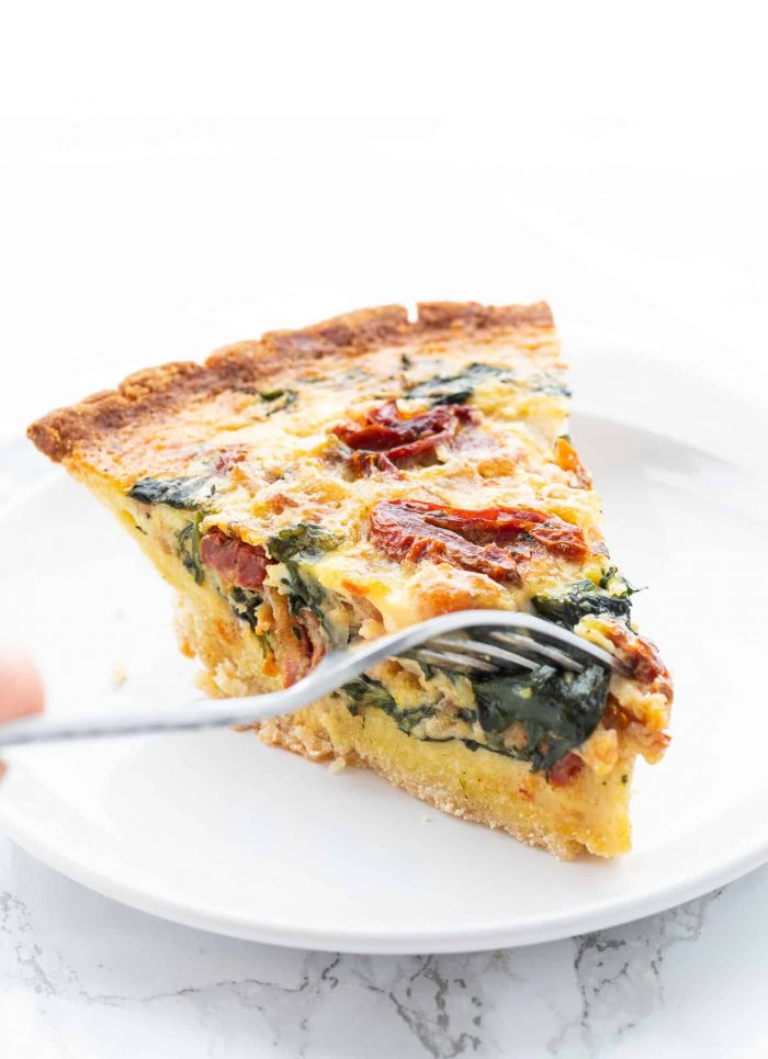eating a slice of spinach bacon quiche