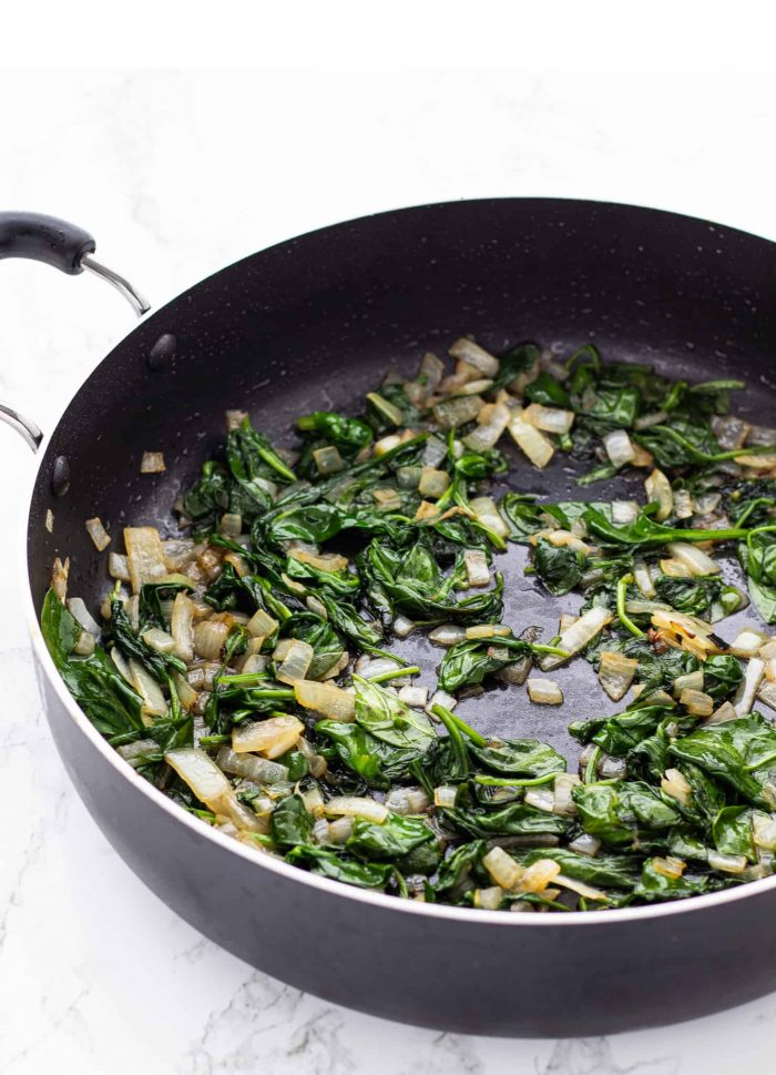 spinach and mushrooms cooking in a skillet