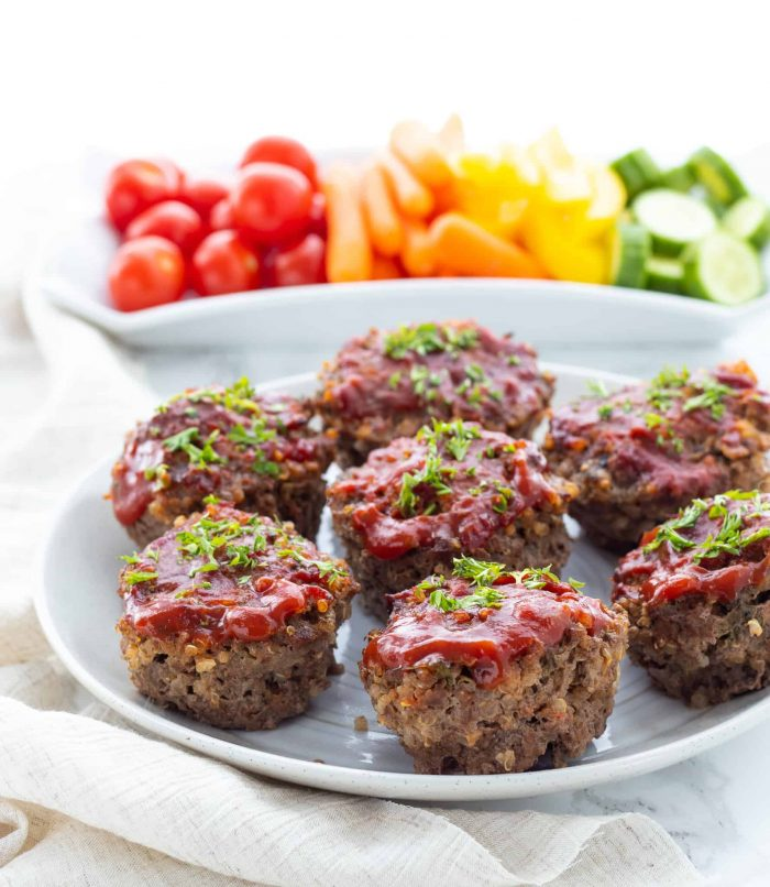 Mini meatloves on a plate topped with sauce and garnished with herbs