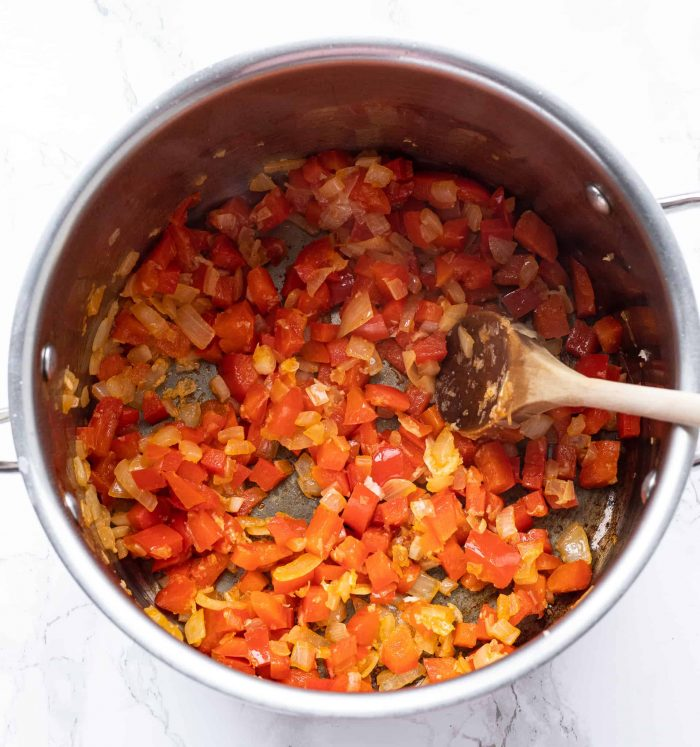 The vegetables being cooked in a large pan