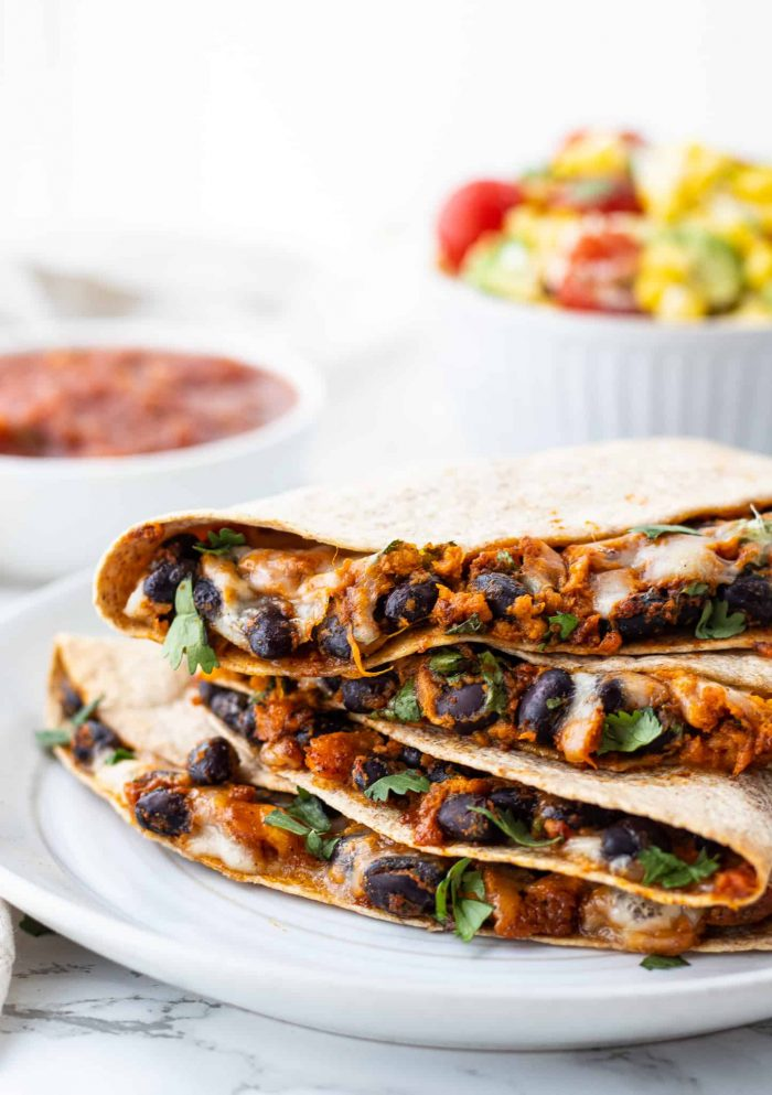 stack of black bean quesadillas with salsa and corn salad