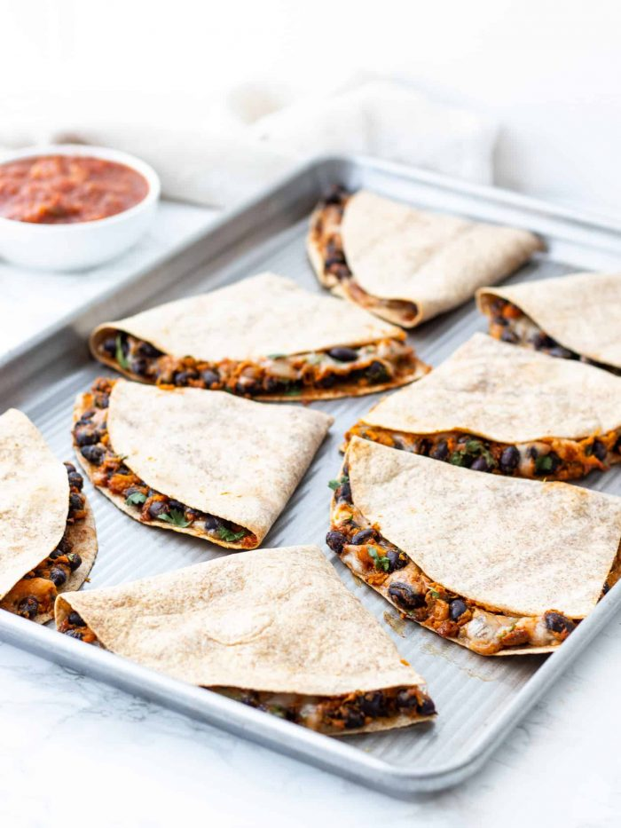 cooked quesadillas cut on a baking sheet
