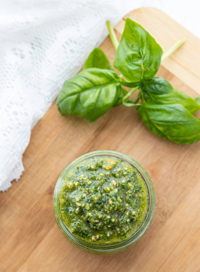 Overhead shot of pesto in a jar next to fresh basil leaves