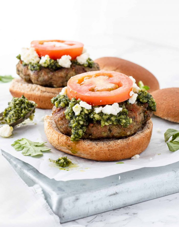 A chicken pesto burger without the top bun on the toppings