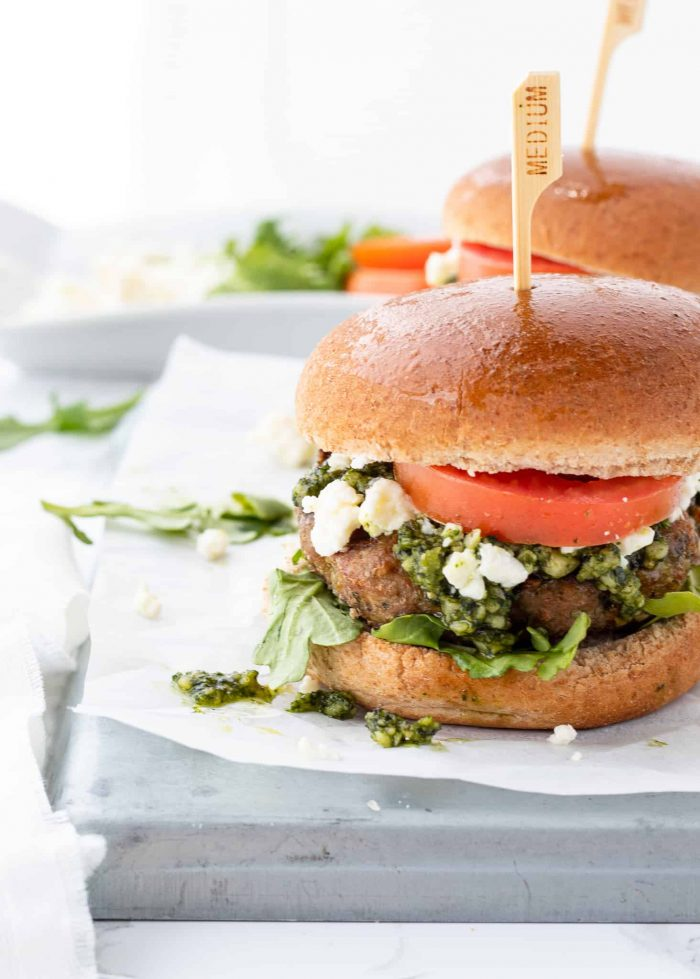 A side view of a chicken pesto burger with toppings