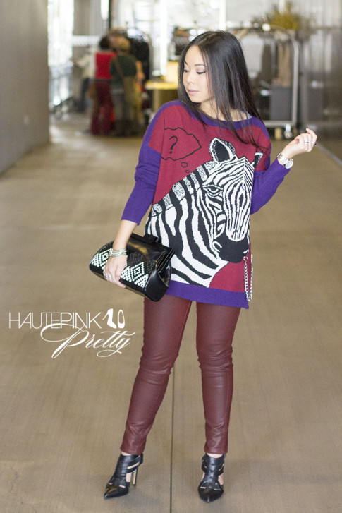 An Dyer wearing Ainsley Zebra TALA INTARSIA PULLOVER, Bleulab Ruby Coated Jeans, ShoeMint Garbo Pumps, Koret Woven Aztec Neo Framed Clutch Glint & Gleam Bracelet