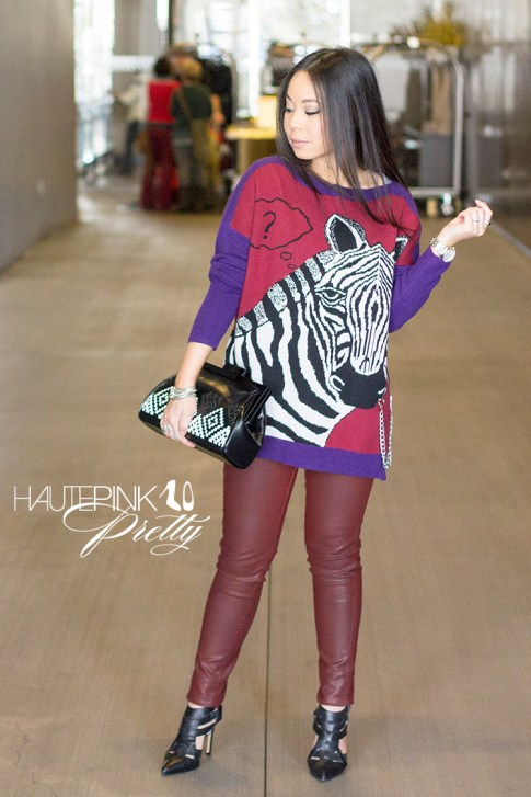 An Dyer wearing Ainsley Zebra TALA INTARSIA PULLOVER, Bleulab Ruby Coated Jeans, ShoeMint Garbo Pumps, Koret Woven Aztec Neo Framed Clutch Glint & Gleam Bracelet