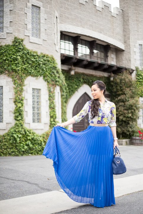 An Dyer wearing Bebe Pleated Long Skirt Maxi Skirt in Nautical Blue Cobalt, Sole Society Kaylin Navy Bag, Zara Blue Floral Blouse, Asos Studded Plate Belt
