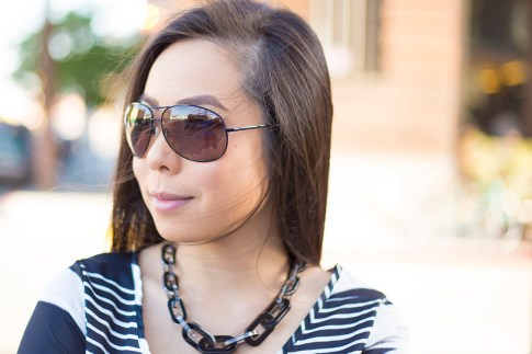 An Dyer wearing Vaunt Black Snake Print Etched Aviator Sunglasses, JewelMint Shadow Link Necklace, Vintage Havana Striped Top