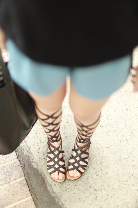 An Dyer wearing Black Knee High Gladiator Sandals