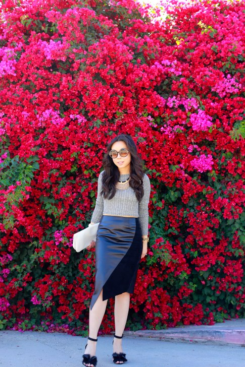 An Dyer Bougainvillea background wearing Khalo BLACK LEATHER BLACK SUEDE ANGULAR SPLIT SKIRT with fur bow sandals toe